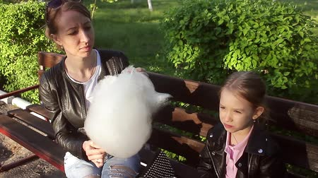 bavlna : Mom and daughter in the park eating cotton candy