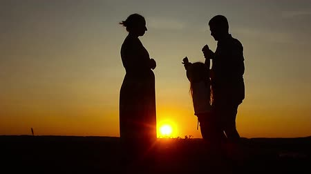 lánya : Silhouette, happy child with mother and father, family at sunset, summertime. Concept of friendly family.
