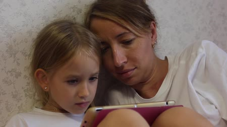 lánya : Charming little girl and her beautiful young mom using a digital tablet and smiling while sitting on sofa at home