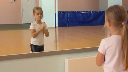 bale : A beautiful girl is engaged in dancing in the dance hall. The child looks at the reflection and performs the exercises. Dancing school.