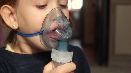 лечит : Sick girl with a sore throat makes inhalation with a mask on his face. Sick patient heals itself nebulizer.