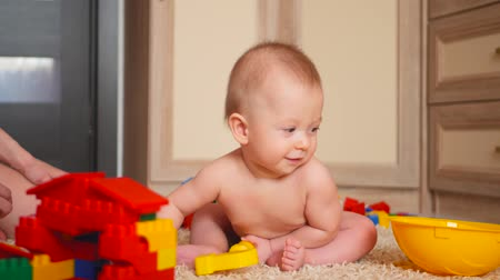 construtor : Small kid boy plays in the constructor, sitting at home on floor Stock Footage