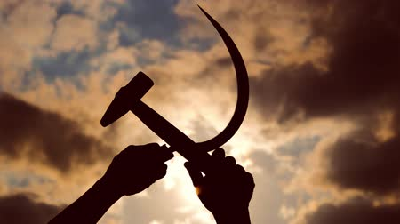 sosyalizm : silhouette of a sickle and a hammer against the sky