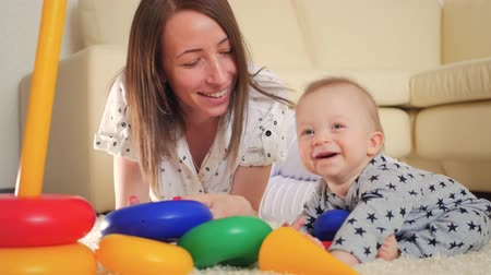 babysitter : Cute mother and child boy play together indoors at home. Loving mom and baby toddler playing and having fun time together. Stock Footage