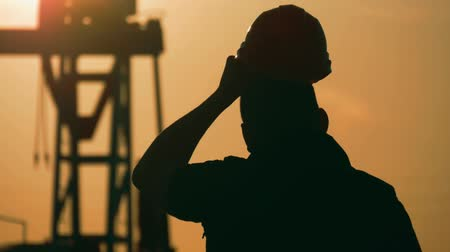 fossil fuel : Oil drill, field pump jack silhouette with setting sun and worker. Oil field, the oil workers are working.