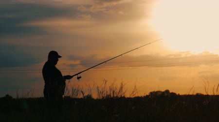 рыболовство : Silhouette fisherman throwing fishing rod in river on background evening sunset. Beautiful evening sunset during fishing on river. Sport hobby fishing.