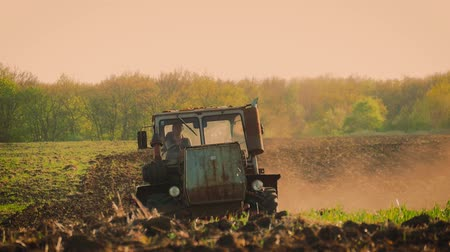 tırmık : Agricultural tractor sowing and cultivating field. Tractor working in the field at sunset. Stok Video
