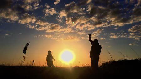 etkinlik : Silhouette of a happy family playing a kite. Grandpa and little girl are playing at sunset with a kite.