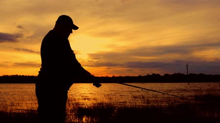 rúd : Silhouette fisherman throws a fishing tackle in the river at dawn. Stock mozgókép