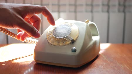 forgó : Close up of male hand picking up the receiver of a vintage retro rotary telephone and answering the phone.