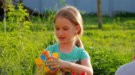 sen : Happy kid playing with toy airplane. Children play in the backyard of the house.