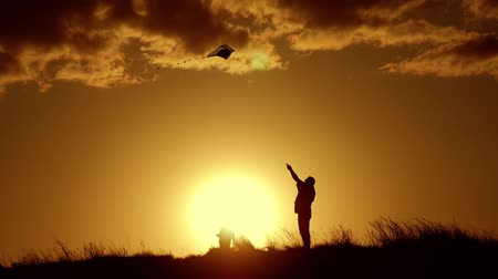 коршун : Silhouette of a happy family playing a kite. Grandpa and little girl are playing at sunset with a kite.