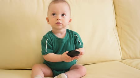 remoto : Little baby boy playing with remote control at home. Little caucasian boy sitting at sofa watching tv set.