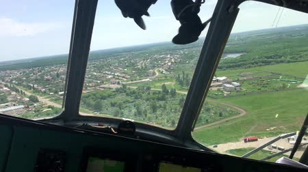 pilótafülke : View from inside of helicopter cockpit of meadows and fields. View from helicopter cabin during flight.