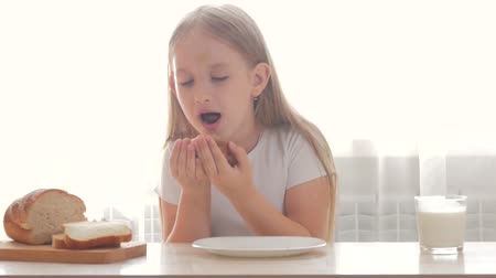 children only : Child drinking milk and eating a sandwich. Girl holding a sandwich and she are to tasting. Stock Footage
