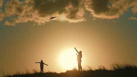 yapıştırma : Silhouette of a happy family playing a kite. Grandpa and little girl are playing at sunset with a kite.