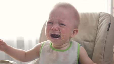 úpadek : Little boy is crying because he doesnt want to eat more cereal. The concept of parents, lifestyle, feeding children. Dostupné videozáznamy