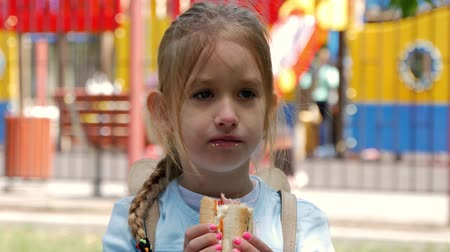 кусаться : Beautiful young girl eating a hot dog in a park.