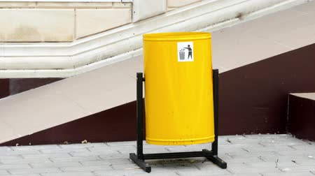 litter box : The public yellow recycling bin on the ground.