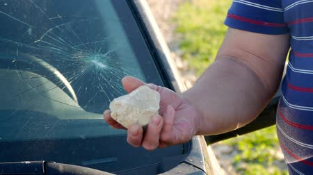 forced : A hand holding a stone after breaking the glass of the car, vandalism. Stock Footage