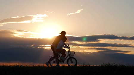 байкер : Silhouette biker lovely family on the meadow at sunset time. Silhouette of mother and baby biking at sunset. Lifestyle Concept.