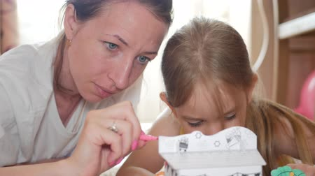 корпус : Young mother and her beautiful daughter, paint a paper house, lying on the floor at home, lifestyle, creativity, education. Стоковые видеозаписи