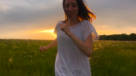 through : Beautiful girl wearing white dress running through beautiful field at sunset. Young woman jogging at the meadow and enjoying freedom. Summer leisure at nature concept.