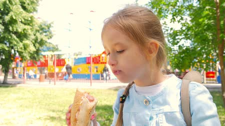 dog bite : Beautiful young girl eating a hot dog in a park.