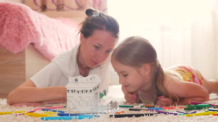 jasně : Young mother and her beautiful daughter, paint a paper house, lying on the floor at home, lifestyle, creativity, education. Dostupné videozáznamy