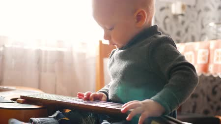 strum : A little boy playing with a guitar at home.