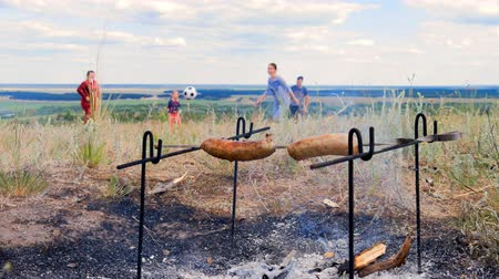 špejle : Close up shot of who cook meat sausages, they are fried in the fire on a meadow on a summer day, fire from a fire cooks a meat dish. Grilled sausages, smoke.