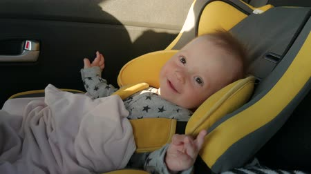 carseat : A cute little baby sits in a car seat, a smile and a joy of travel. Stock Footage