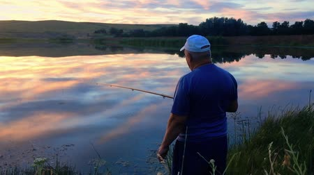 fly fishing : Fisherman with a fishing rod on the shore of the lake at sunset. The man caught the fish on the bait.