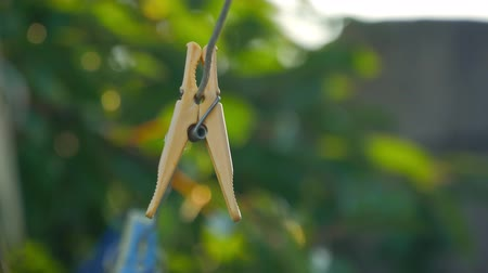 varal : Clips for laundry hanging on a string rope outdoor.