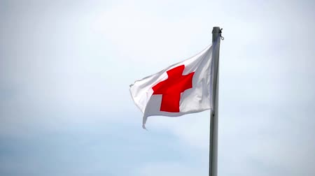 humanitarian : English flag of St George Cross on top of a flagpole, blowing gently in the breeze against a clear blue sky. Stock Footage