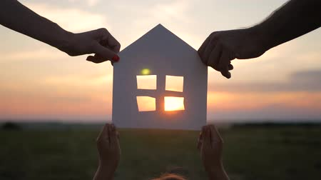 real : Silhouette hands family with paper house at sky sunset background.