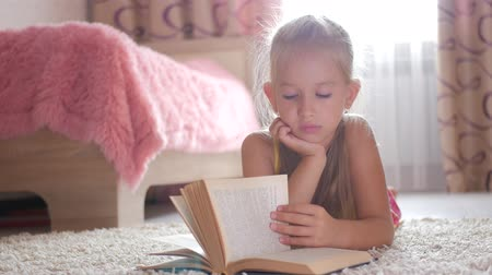 tél : Portrait sad schoolgirl does not want to study and read a book. A sweet blonde girl is sleeping on a book, she is tired when she did her homework. Stock mozgókép