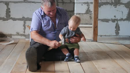 kalapács : Working fun grandfather and grandson on the construction site. Grandfather teaches his grandson the baby to hammer nails. Family concept.
