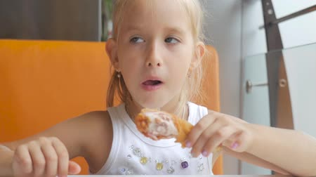 fries : Girl is sitting in a cafe and eating chicken. Concept fast food. Stock Footage