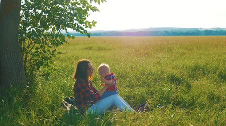 dmuchawiec : Happy young mother playing with her little baby son on sunshine warm autumn or summer day. Happy family concept.