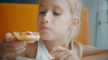 cheese slice : Little girl eating pizza in a fast food restaurant indoors, last piece. Funny little girl eating pizza and smiling at camera.