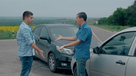 usado : Two drivers argue about blame for accident by the side of damaged. Two male drivers argue over who is to blame for traffic accident. The concept of traffic. Stock Footage