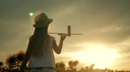 летчик : A girl with hat playing with a wooden airplane. Happy child playing with toy airplane on sunflower field on sunset. In the rays of the sun, the rear view. Baby dream, childhood, memories concept. Стоковые видеозаписи