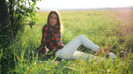 cíle : Young woman sits in a green field at sunset near a ball ball.