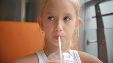 молочный коктейль : Little girl child in cafe drinking milk cocktail cacao with milk. Child drinks a milkshake sits in a cafe.