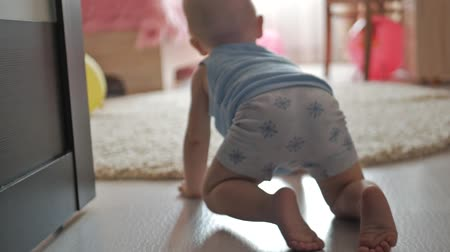 pelenka : funny baby boy crawling on floor at home close-up of the babys legs that creeps towards the toys on the floor