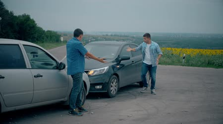 arıza : Two drivers argue about blame for accident by the side of damaged. Two male drivers argue over who is to blame for traffic accident. The concept of traffic. Stok Video