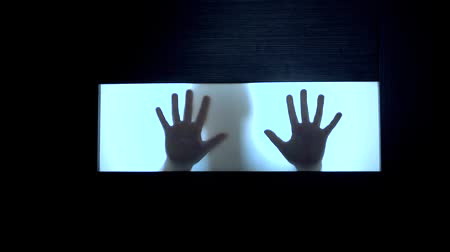 şeytan : Possessed girl scratching glass with hands, creepy female silhouette, horror. Scary ghostly creature behind the glass. Hand hits the matte glass surface. Stok Video