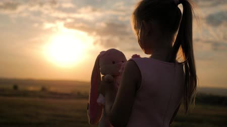кролик : Little girl in pink festive dress holding big plush bunny toy at sunset. Silhouette of a child with a toy. Textile handmade toy bunny in on the girl hand. The concept of a childs dream. Стоковые видеозаписи