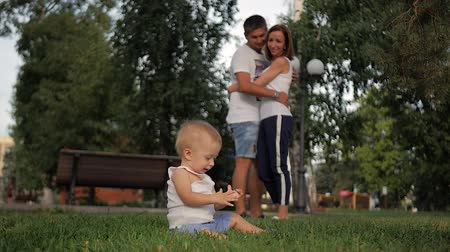sabão : Portrait of happy family - baby boy sits in the park while parents watch him. Concept Family relaxation.
